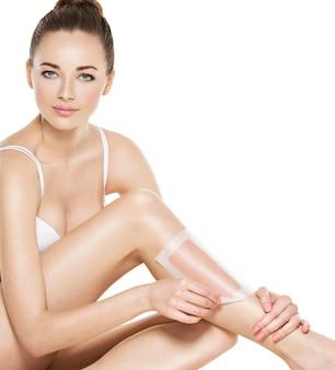 Mulher jovem e bonita depilando as pernas com cera -