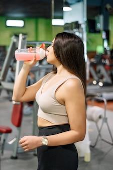 Mulher jovem e bonita descansando e bebendo água no ginásio.