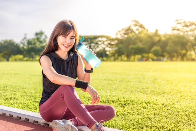 Mulher jovem e bonita descansando para beber água durante o exercício da manhã
