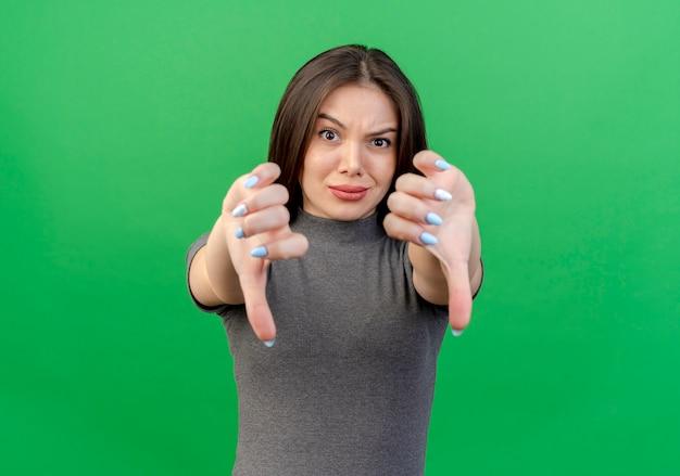 Mulher jovem e bonita descontente mostrando os polegares para baixo, isolados em um fundo verde com espaço de cópia