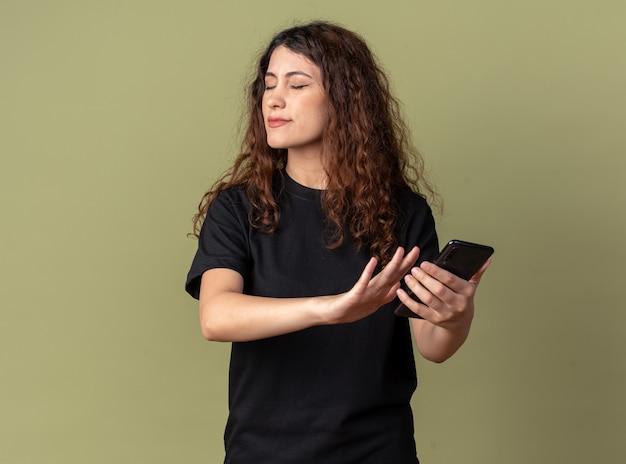 Mulher jovem e bonita descontente segurando um telefone celular, fazendo gesto de recusa com os olhos fechados