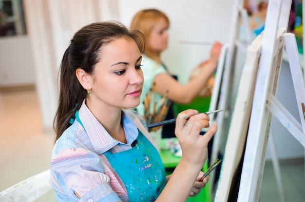 Mulher jovem e bonita desenha pinturas na aula de arte