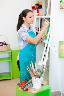 Mulher jovem e bonita desenha uma pintura de pinturas na aula de arte.
