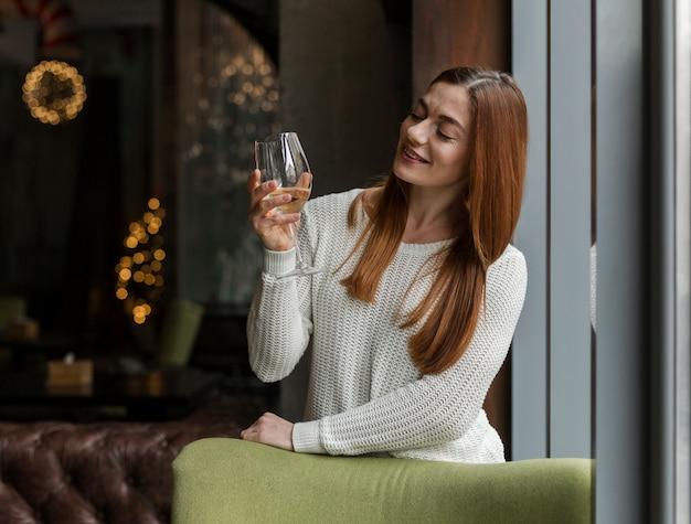 Mulher jovem e bonita desfrutando de copo de vinho