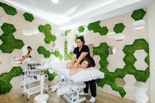 Mulher jovem e bonita desfrutando de massagem cosmetológica profissional
