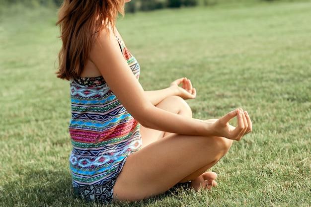 Mulher jovem e bonita desfrutando de meditação e ioga na grama verde no verão na natureza. mulher de beleza fazendo ioga conceito de saudável e ioga. fitness e esportes