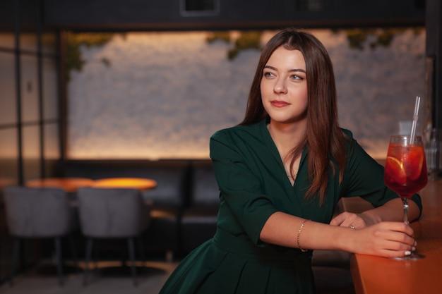 Mulher jovem e bonita desfrutando de relaxar no bar, tomar um cocktail, copie o espaço