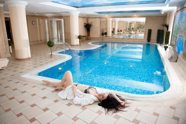 Mulher jovem e bonita desfrutando de spa e piscina
