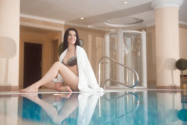 Mulher jovem e bonita desfrutando de spa e piscina.