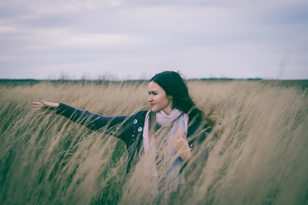Mulher jovem e bonita, desfrutando de um passeio no campo de trigo. foto com espaço de cópia