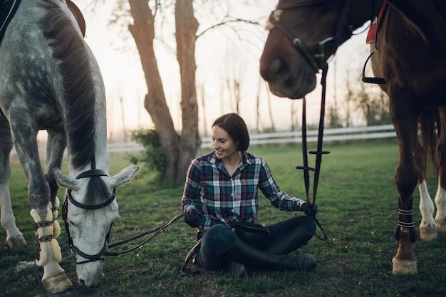 Mulher jovem e bonita desfrutando no rancho com seus dois cavalos. foco seletivo no cavalo branco.
