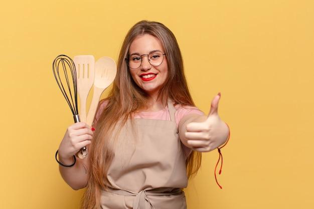 Mulher jovem e bonita desistindo do polegar e segurando utensílios de cozinha