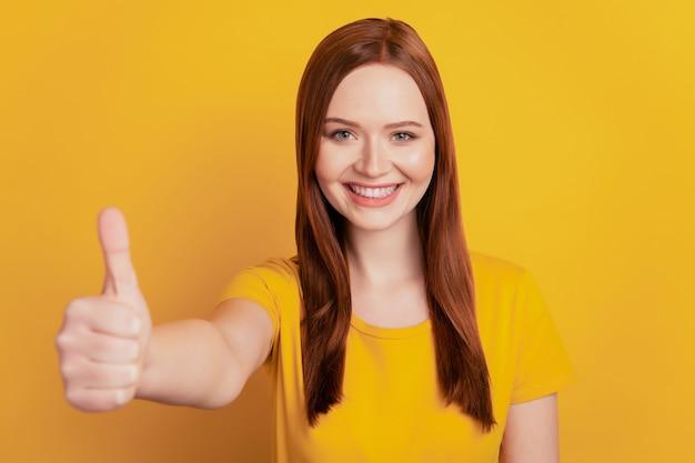 Mulher jovem e bonita desistir do polegar isolado em fundo amarelo