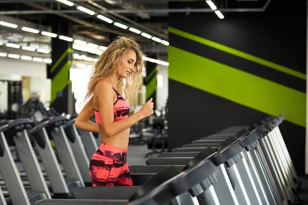Mulher jovem e bonita desportiva correndo na esteira na academia.