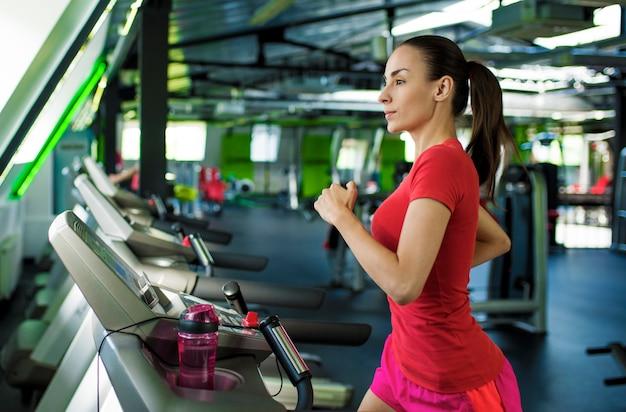 Mulher jovem e bonita desportiva magro em roupas de fitness está correndo na esteira na academia.