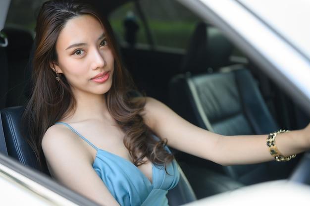 Mulher jovem e bonita dirigindo um carro
