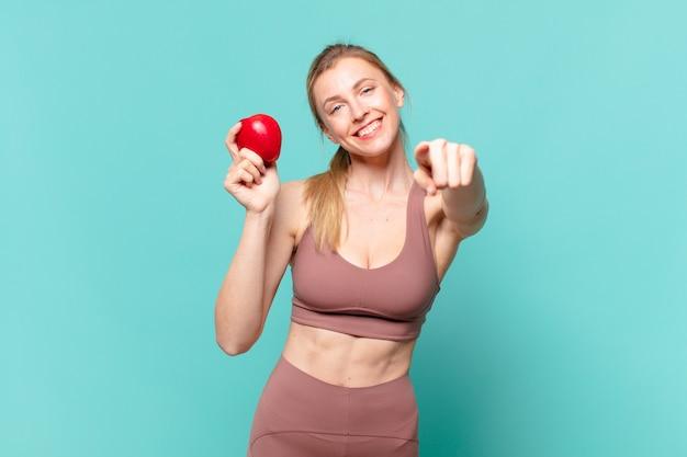 Mulher jovem e bonita do esporte apontando ou mostrando e segurando uma maçã