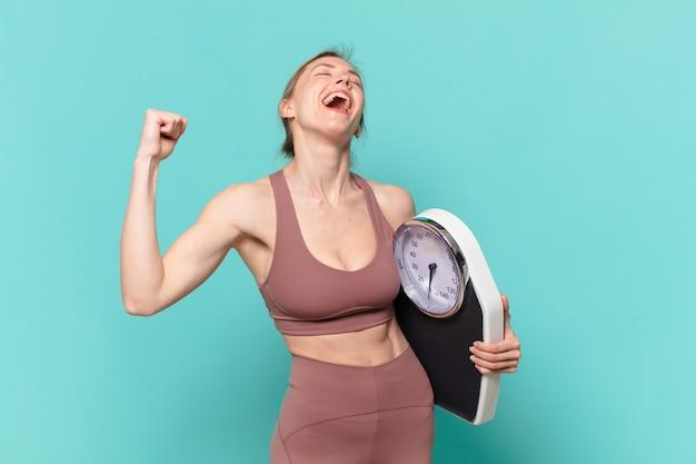 Mulher jovem e bonita do esporte comemorando uma vitória bem-sucedida e segurando uma balança