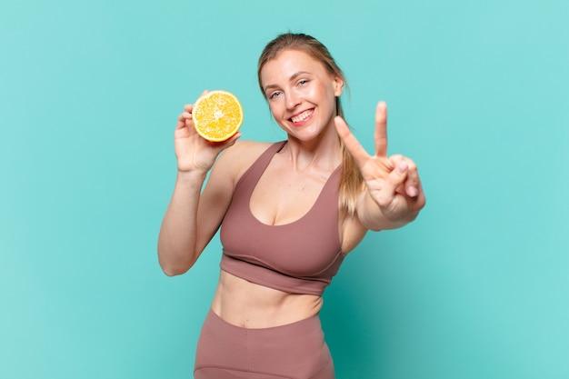 Mulher jovem e bonita do esporte comemorando uma vitória bem-sucedida e segurando uma laranja