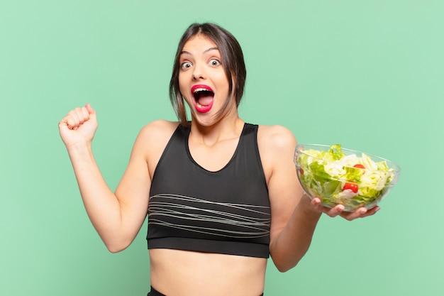 Mulher jovem e bonita do esporte comemorando uma vitória bem-sucedida e segurando uma salada