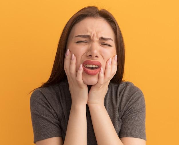 Mulher jovem e bonita dolorida, mantendo as mãos nas bochechas, sofrendo de dor de dente, com os olhos fechados