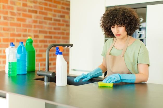 Mulher jovem e bonita dona de casa lavando pratos em casa
