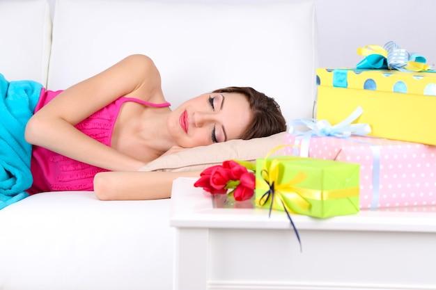 Mulher jovem e bonita dormindo no sofá perto da mesa com presentes e flores, close-up