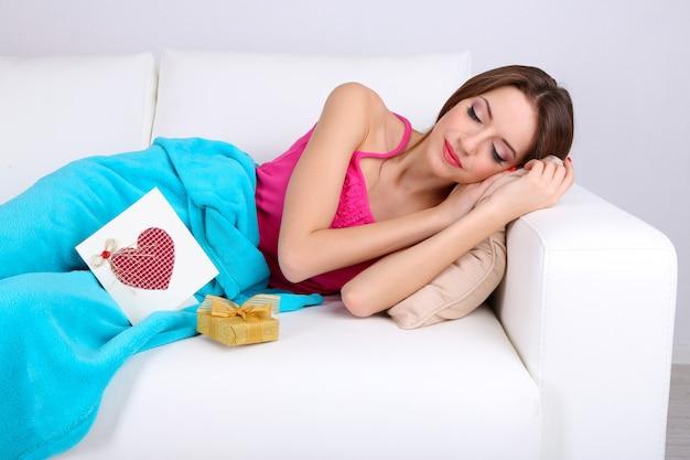 Mulher jovem e bonita dormindo no sofá perto do presente e cartão.