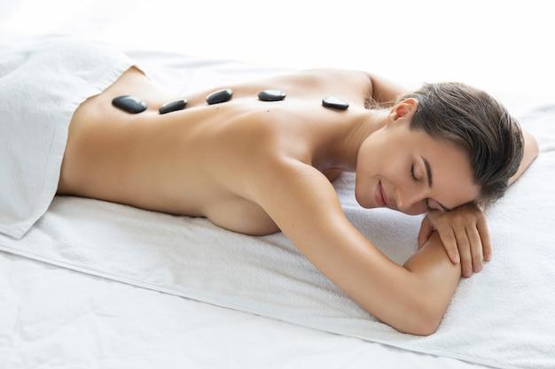 Mulher jovem e bonita durante massagem com pedras quentes