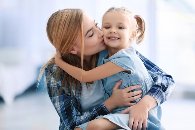 Mulher jovem e bonita e a filha em casa.