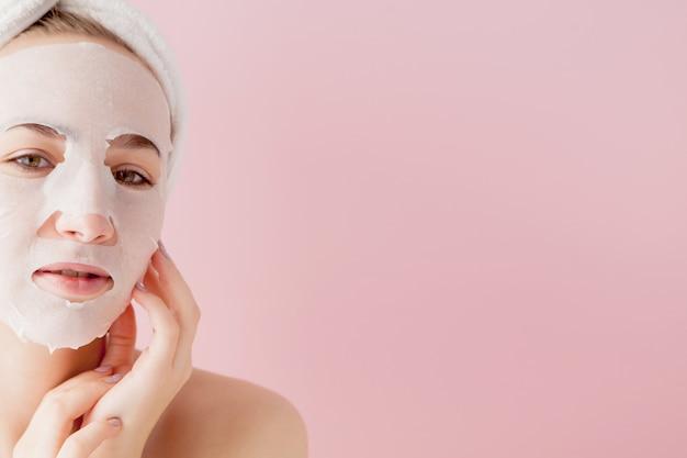 Mulher jovem e bonita é aplicar uma máscara de tecido cosmético em um rosto em um fundo rosa