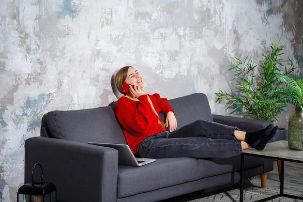 Mulher jovem e bonita e atraente está sentada em casa no sofá e falando ao telefone, ela está vestida com um suéter vermelho e calça jeans, ao lado de um laptop