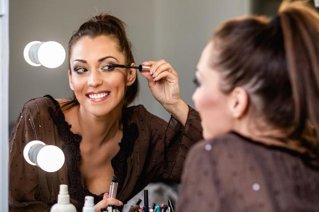 Mulher jovem e bonita e beleza profissional compõem um tutorial de maquiagem de gravação de vlogger ou blogger para compartilhar no site ou nas redes sociais.