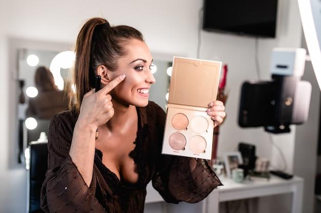 Mulher jovem e bonita e beleza profissional compõem um tutorial de maquiagem de vlogger ou blogger de gravação de artista para compartilhar em um site ou mídia social