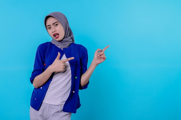 Mulher jovem e bonita e carismática com um hijab apontando isolado em um fundo azul claro