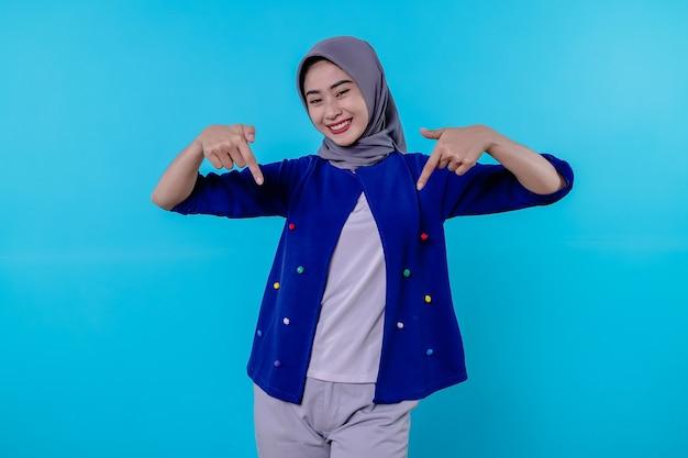Mulher jovem e bonita e carismática com um hijab apontando para baixo, isolado em um fundo azul claro