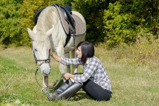Mulher jovem e bonita e cavalo branco