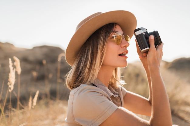 Mulher jovem e bonita e elegante em um vestido cáqui no deserto, viajando pela áfrica em um safári, usando um chapéu, tirando foto com uma câmera vintage