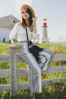 Mulher jovem e bonita e elegante, tendência da moda primavera verão, estilo boho, chapéu de palha, fim de semana no campo, ensolarado, sorridente, divertido, bolsa preta, calças listradas