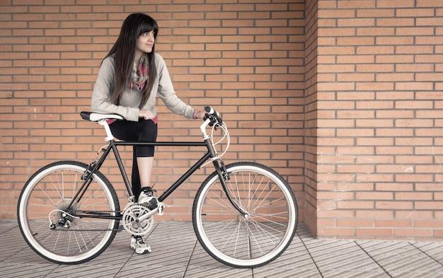 Mulher jovem e bonita e esportiva posando com uma bicicleta fixie personalizada sobre uma parede de tijolos laranja no fundo