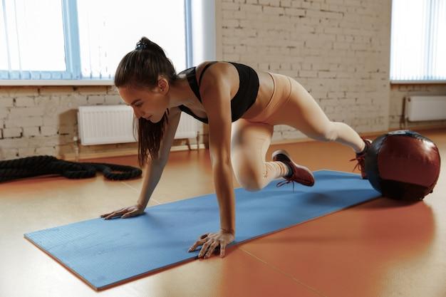 Mulher jovem e bonita e magra fazendo ginástica na academia com medball