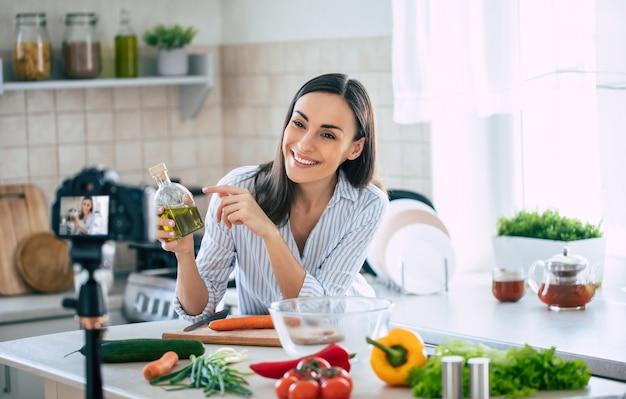 Mulher jovem e bonita e profissional, feliz, está escrevendo para seu canal de cozinha sobre a vida saudável na cozinha de sua casa e olhando para a câmera em um tripé