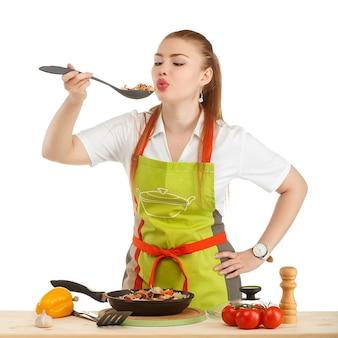 Mulher jovem e bonita e sexy cozinhando uma refeição fresca isolada no branco
