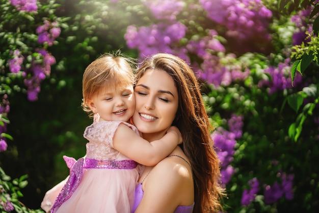 Mulher jovem e bonita e sua filha encantadora estão abraçando e sorrindo. dia das mães