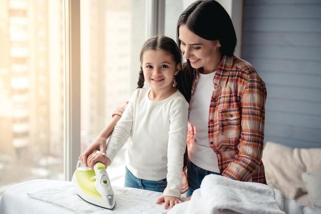 Mulher jovem e bonita e sua filha estão sorrindo