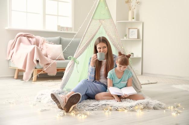 Mulher jovem e bonita e sua filha lendo um livro em casa
