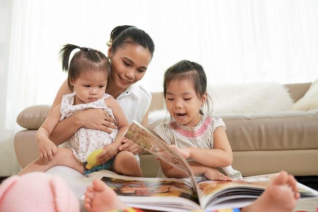 Mulher jovem e bonita e suas duas filhas pequenas virando as páginas de um álbum com fotos antigas