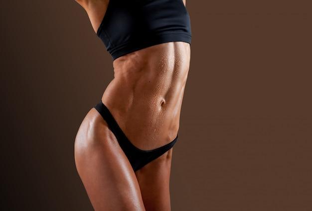 Mulher jovem e bonita e super em forma exibindo seu abdômen musculoso perfeito.