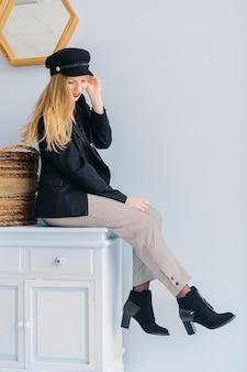 Mulher jovem e bonita elegante com longos cabelos loiros encaracolados em jaqueta preta e calça xadrez senta-se na cômoda no interior acolhedor.