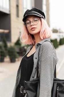 Mulher jovem e bonita elegante com óculos e um cocar em uma camiseta preta com uma camisa da moda e uma bolsa caminha na rua